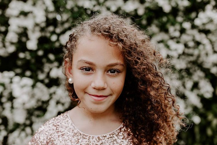 Beautiful flower girl with naturally curly hair