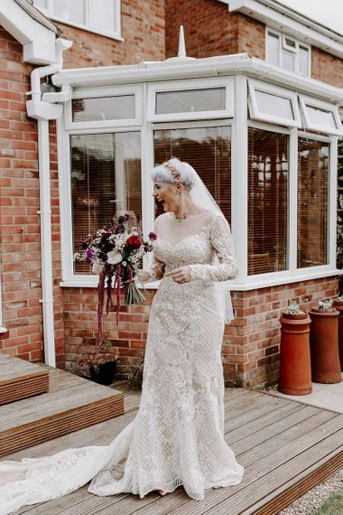 Boho bride in lace Lillian West wedding dress with long sleeves