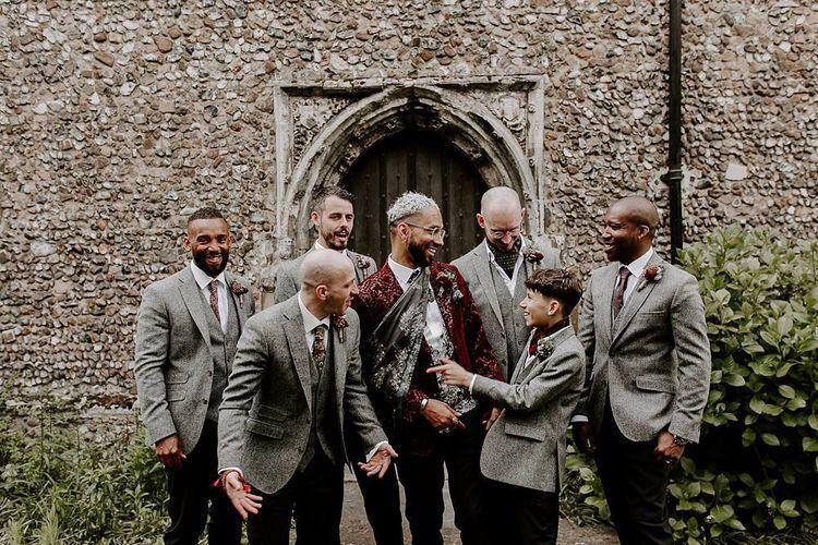 Groom in pink blazer and groomsmen in grey waistcoats and jackets