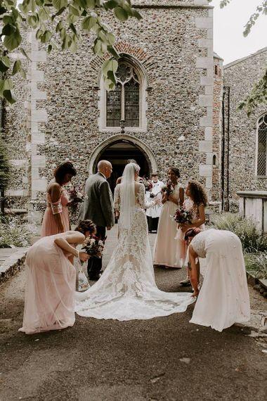 Bride in Lillian West wedding dress outside the church