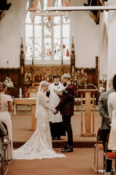 Bride and groom standing at the altar holding hands