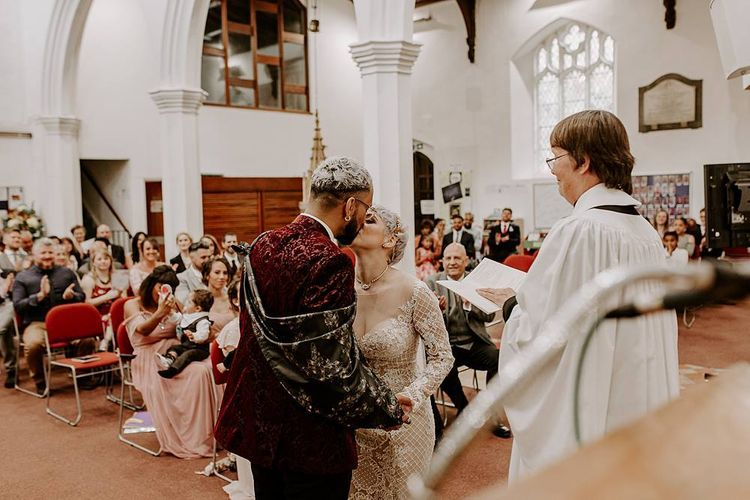 Groom in red blazer and bride in Lillian West wedding dress kissing at the altar