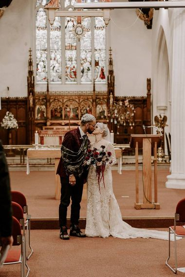 Stylish bride and groom kissing during the wedding ceremony