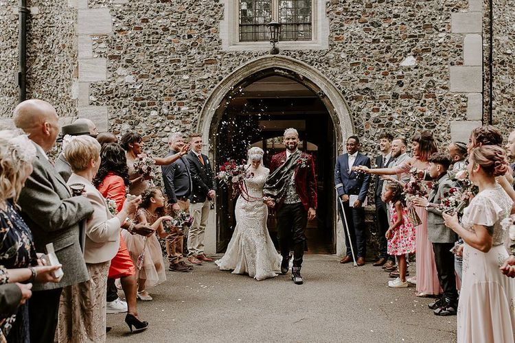 Bride and groom confetti exit with bride in lace Lillian West wedding dress