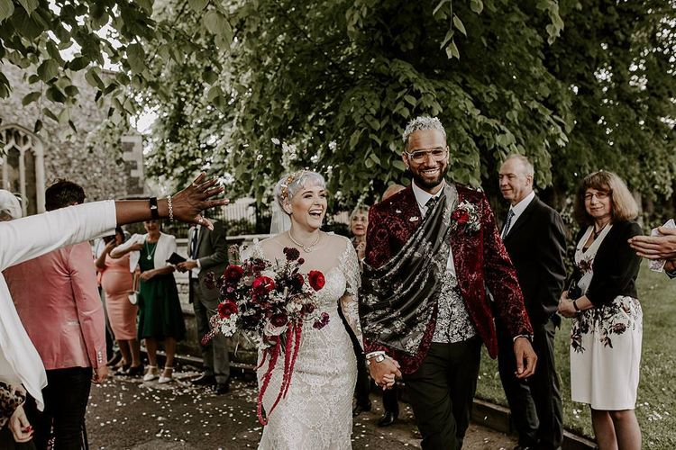Stylish bride and groom confetti exit with bride in Lillian West wedding dress