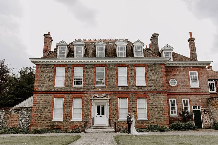 Bride and groom portrait outside their wedding venue Abbots Hall, Suffolk