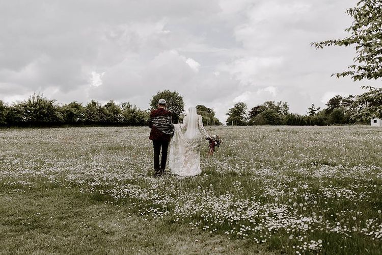 Bride and groom walking through the fields