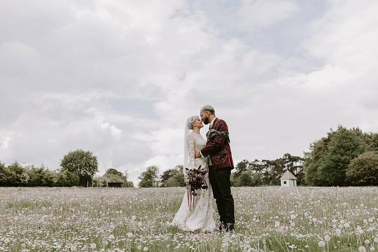 Stylish bride and groom portrait kissing in the fields