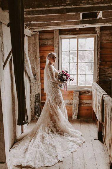 Bride in Lillian West wedding dress with illusion neckline and long sleeves