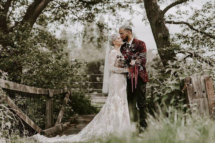 Groom in a velvet blazer kissing his bride in a lace Lillian West wedding dress