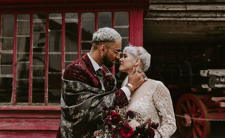 Stylish groom in red blazer and silk shawl kissing his bride