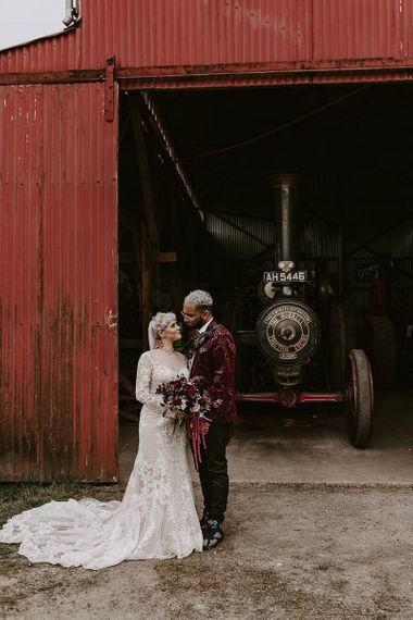 Bride in Lillian West wedding dress and groom in pink blazer next to a steam engine