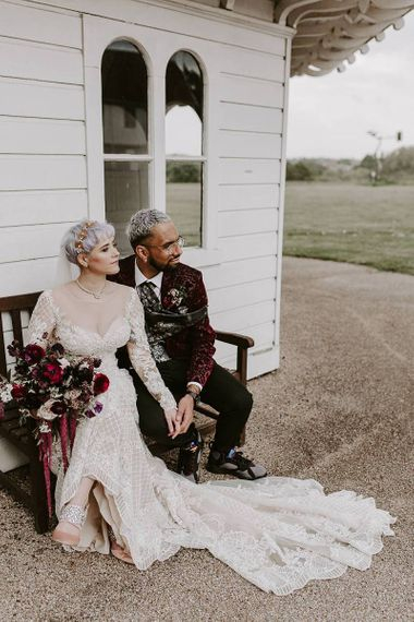 Stylish bride and groom sitting on a bench together with bride in Lillian West wedding dress