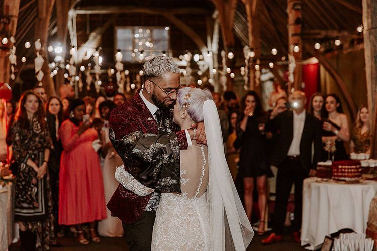 Bride and groom first dance in a festoon lit barn with bride in Lillian West wedding dress