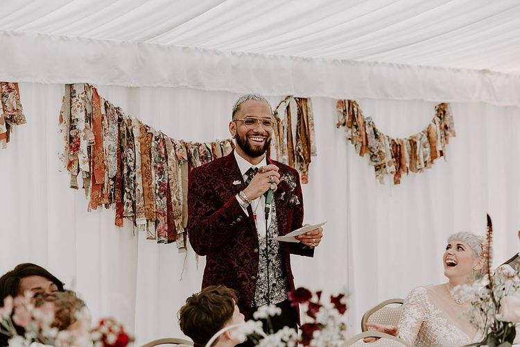Groom giving a wedding speech with fabric bunting backdrop