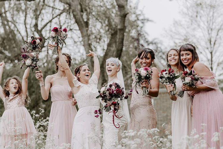 Fun bridal party portrait with bridesmaids in pink dresses and bride in Lillian West dress