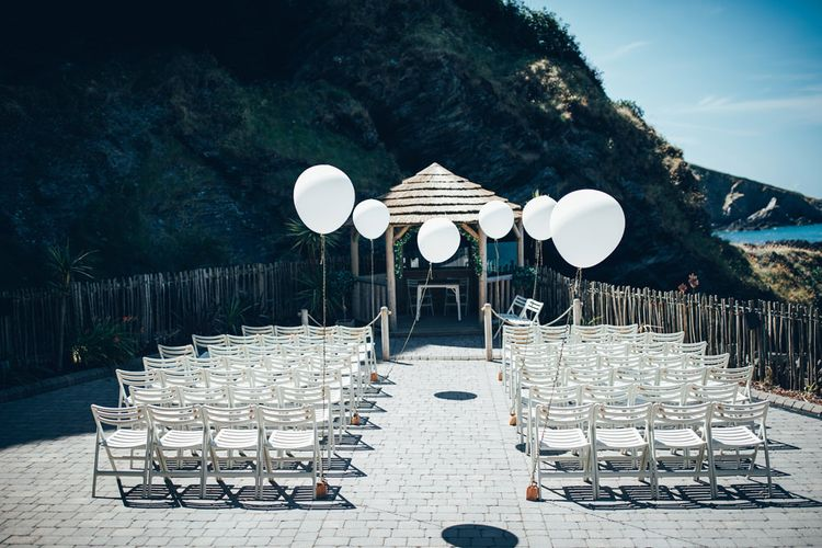 Oversized White Balloons | Gypsophila Wedding Arch | White Chairs | Wedding Ceremony Décor for Nuptials by the Sea | Gypsophila Arch and Giant Balloons for an Outdoor Coastal Wedding | Toby Lowe Photography