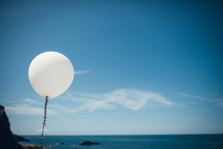 Oversized White Balloon with Foliage Trail | Gypsophila Arch and Giant Balloons for an Outdoor Coastal Wedding | Toby Lowe Photography