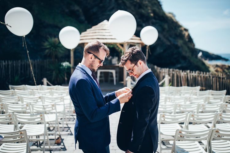 Buttonhole Being Pinned to Groom's Suit | Groom in Navy Suit | Gypsophila Arch and Giant Balloons for an Outdoor Coastal Wedding | Toby Lowe Photography