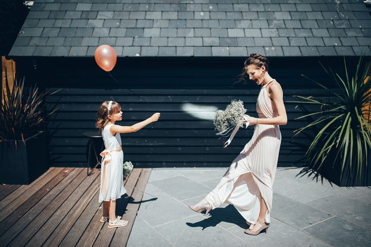 Bridesmaid in Soft Pink ASOS Halterneck Dress | Gypsophila Bouquets Tied with Pink Trailing Ribbon | Sequined Pink Shoes | Flower Girl in White Dress with Pink Sash | Pink Balloon with Black String | Gypsophila Arch and Giant Balloons for an Outdoor Coastal Wedding | Toby Lowe Photography