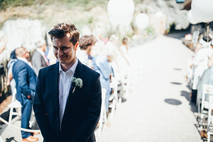 Groom in Navy Blue Suit | Gypsophila Buttonhole | Groom Waiting at Altar | Gypsophila Arch and Giant Balloons for an Outdoor Coastal Wedding | Toby Lowe Photography