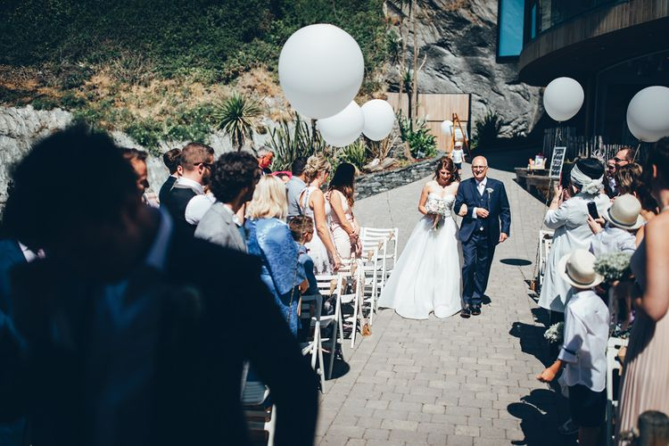 Bride in Strapless Ballgown Dress by Pronovias with Crystal Belt | Bridal Bouquet of Pink Gerberas, White Gerberas and Gypsophila Tied with Pink Trailing Ribbon | Father of the Bride in Navy Three Piece Suit with Pink Tie | Oversized White Balloons with Foliage String | Arrival of the Bride | Gypsophila Arch and Giant Balloons for an Outdoor Coastal Wedding | Toby Lowe Photography