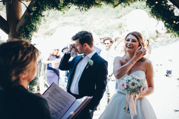 Bride in Strapless Ballgown Dress by Pronovias with Crystal Belt | Bridal Bouquet of Pink Gerberas, White Gerberas and Gypsophila Tied with Pink Trailing Ribbon | Groom in Navy Suit with Gypsophila Buttonhole | Gypsophila Wedding Arch with Fairy Lights | Wedding Ceremony Emotions | Gypsophila Arch and Giant Balloons for an Outdoor Coastal Wedding | Toby Lowe Photography