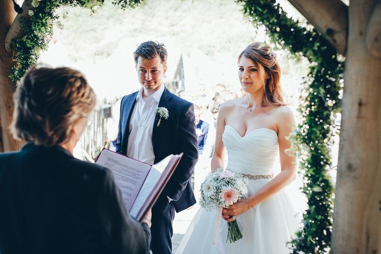 Bride in Strapless Ballgown Dress by Pronovias with Crystal Belt | Bridal Bouquet of Pink Gerberas, White Gerberas and Gypsophila Tied with Pink Trailing Ribbon | Groom in Navy Suit with Gypsophila Buttonhole | Gypsophila Wedding Arch with Fairy Lights | Wedding Ceremony | Gypsophila Arch and Giant Balloons for an Outdoor Coastal Wedding | Toby Lowe Photography