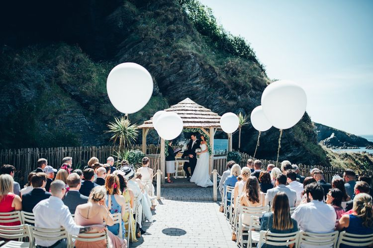 Oversized White Balloons with Foliage String | Bride in Strapless Ballgown Dress by Pronovias with Crystal Belt | Bridal Bouquet of Pink Gerberas, White Gerberas and Gypsophila Tied with Pink Trailing Ribbon | Groom in Navy Suit with Gypsophila Buttonhole | Gypsophila Wedding Arch with Fairy Lights | Wedding Ceremony | Gypsophila Arch and Giant Balloons for an Outdoor Coastal Wedding | Toby Lowe Photography