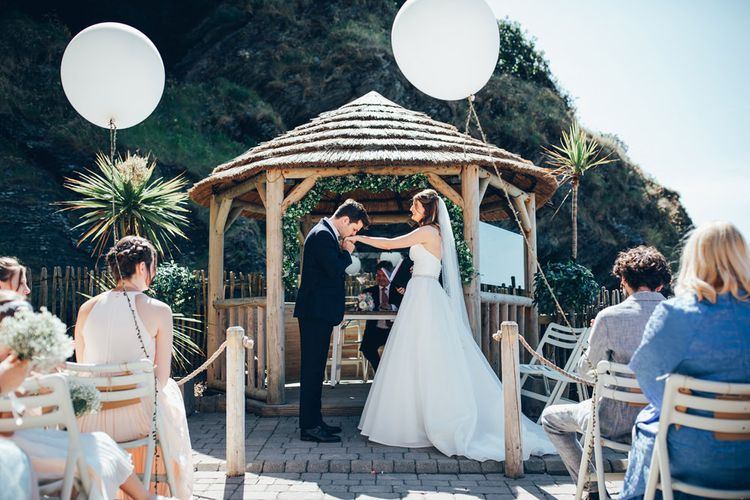Bride in Strapless Ballgown Dress by Pronovias with Crystal Belt | Fingertip Veil | Groom in Navy Suit with Gypsophila Buttonhole | Oversized White Balloons with Foliage String | Gypsophila Wedding Arch with Fairy Lights | Wedding Ceremony | Gypsophila Arch and Giant Balloons for an Outdoor Coastal Wedding | Toby Lowe Photography