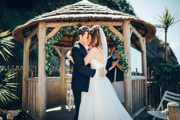 Bride in Strapless Ballgown Dress by Pronovias with Crystal Belt | Fingertip Veil | Groom in Navy Suit with Gypsophila Buttonhole | Gypsophila Wedding Arch | Wedding Ceremony | Gypsophila Arch and Giant Balloons for an Outdoor Coastal Wedding | Toby Lowe Photography