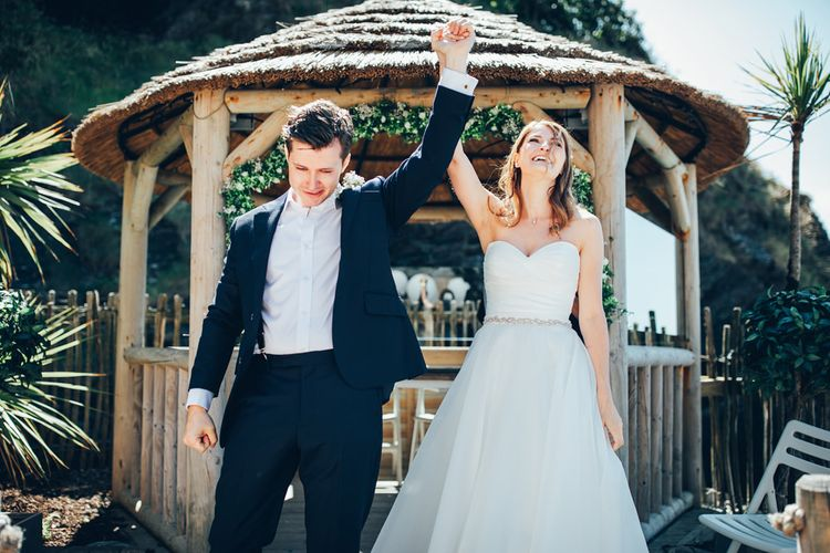 Bride in Strapless Ballgown Dress by Pronovias with Crystal Belt | Groom in Navy Suit with Gypsophila Buttonhole | Gypsophila Wedding Arch | Wedding Ceremony | Gypsophila Arch and Giant Balloons for an Outdoor Coastal Wedding | Toby Lowe Photography