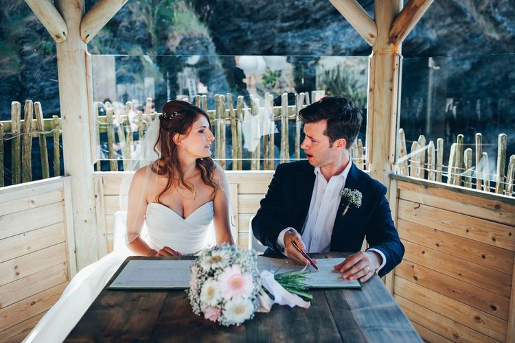 Bride in Strapless Ballgown Dress by Pronovias with Crystal Belt | Fingertip Veil | Bridal Bouquet of Pink Gerberas, White Gerberas and Gypsophila Tied with Pink Trailing Ribbon | Groom in Navy Suit with Gypsophila Buttonhole | Signing of the Register | Gypsophila Arch and Giant Balloons for an Outdoor Coastal Wedding | Toby Lowe Photography