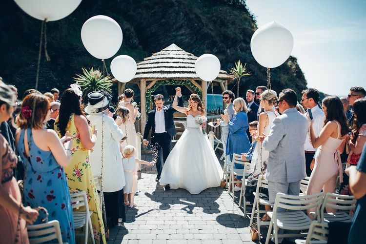 Bride in Strapless Ballgown Dress by Pronovias with Crystal Belt | Bridal Bouquet of Pink Gerberas, White Gerberas and Gypsophila Tied with Pink Trailing Ribbon | Groom in Navy Suit with Gypsophila Buttonhole | Oversized White Balloons with Foliage String | Gypsophila Wedding Arch | Just Married | Gypsophila Arch and Giant Balloons for an Outdoor Coastal Wedding | Toby Lowe Photography