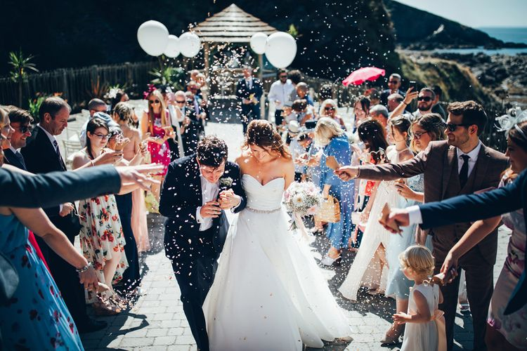 Bride in Strapless Ballgown Dress by Pronovias with Crystal Belt | Bridal Bouquet of Pink Gerberas, White Gerberas and Gypsophila Tied with Pink Trailing Ribbon | Groom in Navy Suit with Gypsophila Buttonhole | Confetti Throw | Oversized White Balloons with Foliage String | Gypsophila Arch and Giant Balloons for an Outdoor Coastal Wedding | Toby Lowe Photography