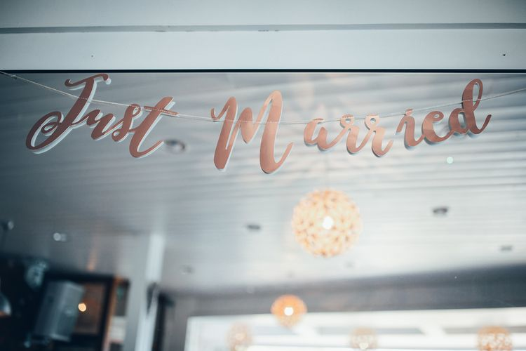 Copper Just Married Banner | Wedding Reception Décor | Gypsophila Arch and Giant Balloons for an Outdoor Coastal Wedding | Toby Lowe Photography