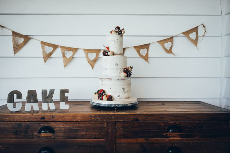 Three-Tier Semi-Naked Cake with Chocolate Dipped Strawberries | Hessian Bunting with White Hearts | Gypsophila Arch and Giant Balloons for an Outdoor Coastal Wedding | Toby Lowe Photography