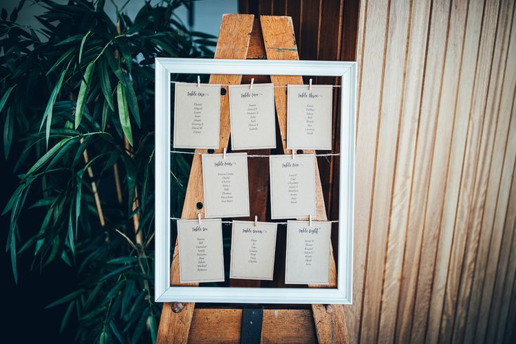 Wedding Reception Table Plan | Wooden Easel | White Picture Frame | Gypsophila Arch and Giant Balloons for an Outdoor Coastal Wedding | Toby Lowe Photography