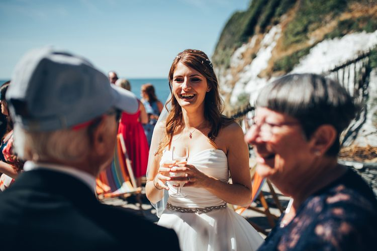 Bride in Strapless Ballgown Dress by Pronovias with Crystal Belt | Wedding Reception Drinks at Tunnels Beaches in Devon | Gypsophila Arch and Giant Balloons for an Outdoor Coastal Wedding | Toby Lowe Photography