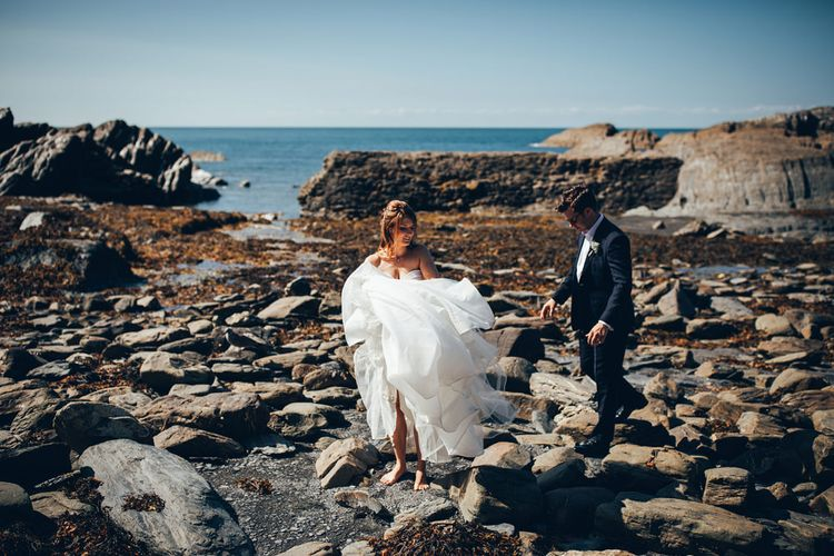 Bride in Strapless Ballgown Dress by Pronovias with Crystal Belt | Groom in Navy Suit with Gypsophila Buttonhole | Gypsophila Arch and Giant Balloons for an Outdoor Coastal Wedding | Toby Lowe Photography