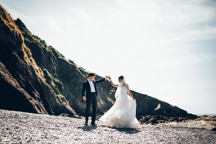 Bride in Strapless Ballgown Dress by Pronovias with Crystal Belt | Fingertip Veil | Groom in Navy Suit with Gypsophila Buttonhole | Gypsophila Arch and Giant Balloons for an Outdoor Coastal Wedding | Toby Lowe Photography