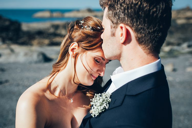 Bride in Strapless Ballgown Dress by Pronovias with Crystal Belt | Delicate Silver Hair Vine with Pearls and Crystals | Groom in Navy Suit with Gypsophila Buttonhole | Gypsophila Arch and Giant Balloons for an Outdoor Coastal Wedding | Toby Lowe Photography