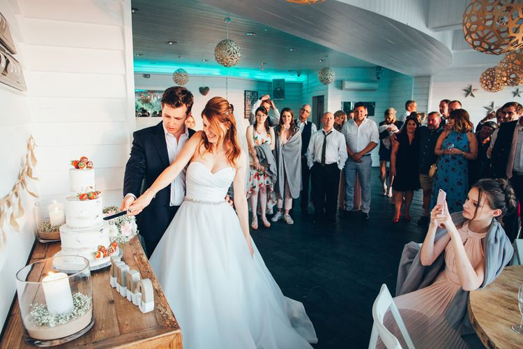 Bride in Strapless Ballgown Dress by Pronovias with Crystal Belt | FingertipGypsophila Arch and Giant Balloons for an Outdoor Coastal Wedding | Strapless Ballgown Dress by Pronovias with Crystal Belt | Fingertip Veil | Silver Hair Vine | Soft Pink ASOS Halterneck Dresses | Navy Suits | Gypsophila Buttonhole | Bouquet of Pink Gerberas, White Gerberas and Gypsophila with Pink Trailing Ribbon | Gypsophila Bouquets with Pink Trailing Ribbon | Oversized White Balloons | Semi-Naked Cake | Golden Hour Photos | Toby Lowe Photography Veil | Groom in Navy Suit with Gypsophila Buttonhole |  Cutting of the Cake | Gypsophila Arch and Giant Balloons for an Outdoor Coastal Wedding | Toby Lowe Photography