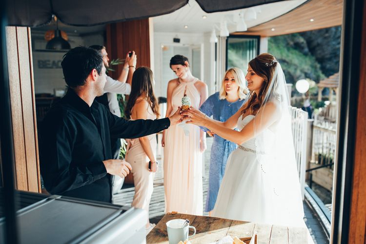 Bride in Strapless Ballgown Dress by Pronovias with Crystal Belt | Fingertip Veil | Bridesmaid in Soft Pink ASOS Halterneck Dress | Ice Cream Cart | Gypsophila Arch and Giant Balloons for an Outdoor Coastal Wedding | Toby Lowe Photography