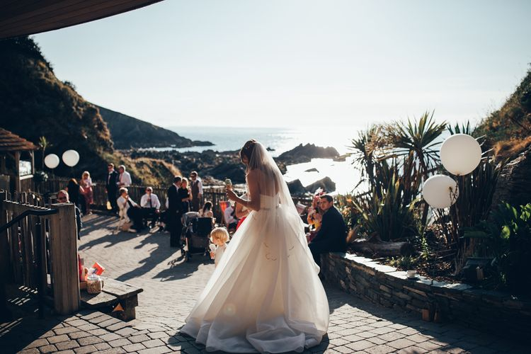 Bride in Strapless Ballgown Dress by Pronovias with Crystal Belt | Fingertip Veil | Ice Cream | Gypsophila Arch and Giant Balloons for an Outdoor Coastal Wedding | Toby Lowe Photography