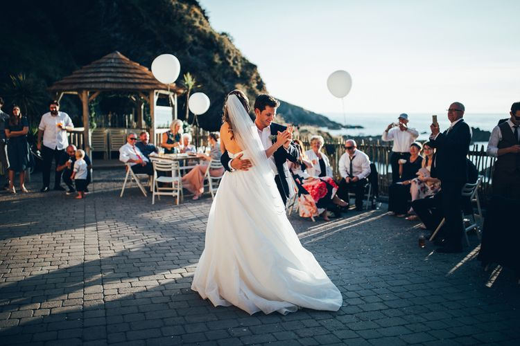 Bride in Strapless Ballgown Dress by Pronovias with Crystal Belt | Fingertip Veil | Groom in Navy Suit with Gypsophila Buttonhole | Oversized White Balloons with Foliage String | First Dance | Gypsophila Arch and Giant Balloons for an Outdoor Coastal Wedding | Toby Lowe Photography
