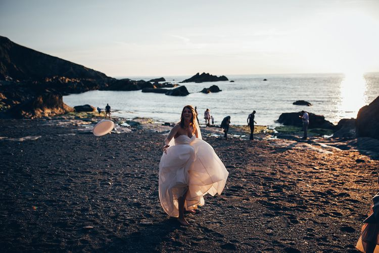 Bride in Strapless Ballgown Dress by Pronovias with Crystal Belt | Frisbee | Gypsophila Arch and Giant Balloons for an Outdoor Coastal Wedding | Toby Lowe Photography