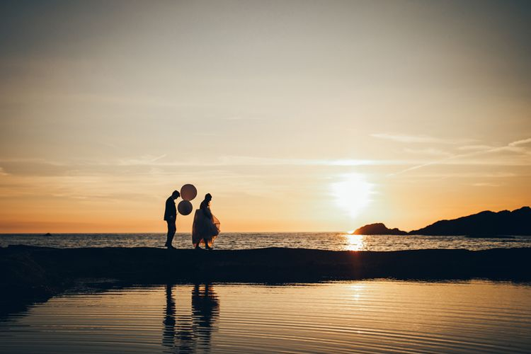 Bride in Strapless Ballgown Dress by Pronovias with Crystal Belt | Groom in Navy Suit with Gypsophila Buttonhole | Oversized White Balloons | Golden Hour Photos | Gypsophila Arch and Giant Balloons for an Outdoor Coastal Wedding | Toby Lowe Photography