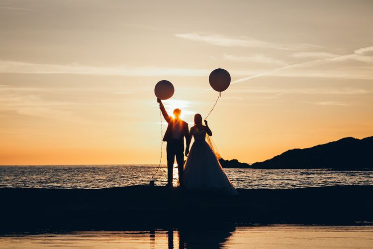 Bride in Strapless Ballgown Dress by Pronovias with Crystal Belt | Fingertip Veil | Groom in Navy Suit with Gypsophila Buttonhole |  Oversized White Balloons | Golden Hour Photos | Gypsophila Arch and Giant Balloons for an Outdoor Coastal Wedding | Toby Lowe Photography