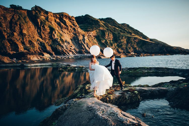 Bride in Strapless Ballgown Dress by Pronovias with Crystal Belt | Fingertip Veil | Groom in Navy Suit with Gypsophila Buttonhole |  Oversized White Balloons | Gypsophila Arch and Giant Balloons for an Outdoor Coastal Wedding | Toby Lowe Photography